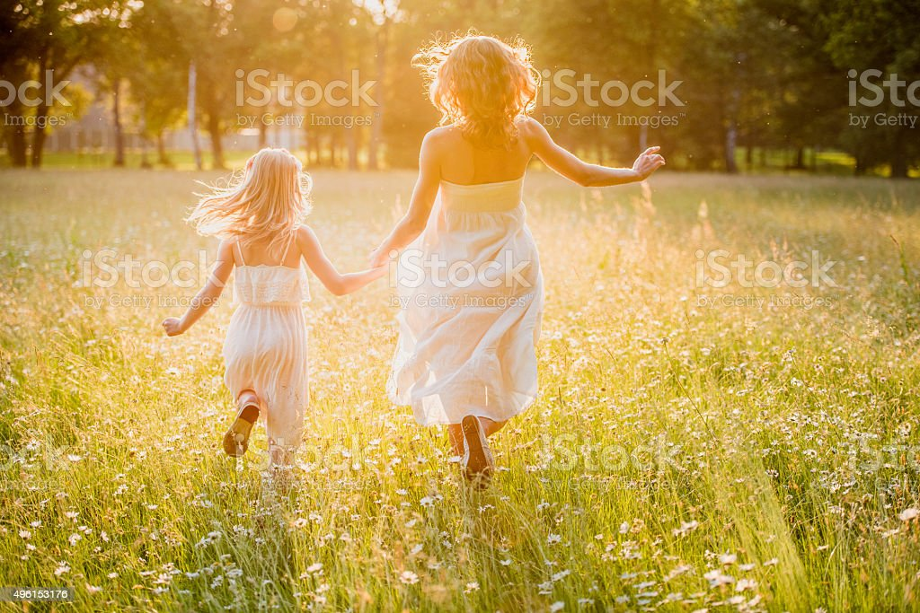 Mother and little daughter running across a golden meadow stock photo