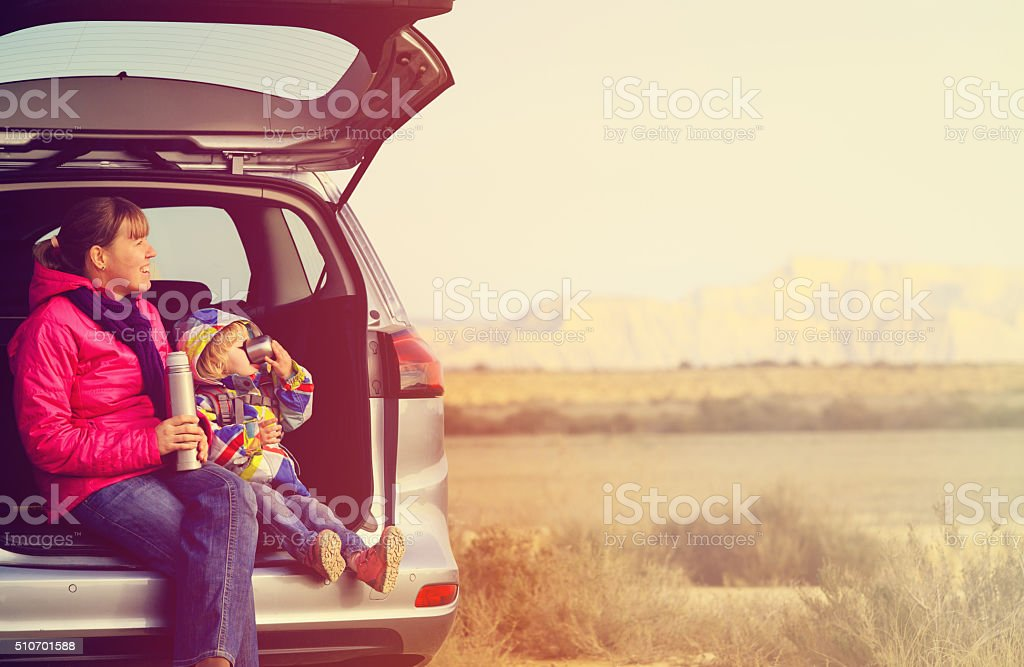 mother and little daughter travel by car in mountains stock photo