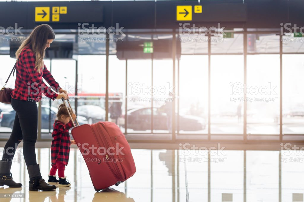 Mother and little daughter walking in the airport stock photo