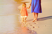 Mother and daughter playing on the beach holding hands