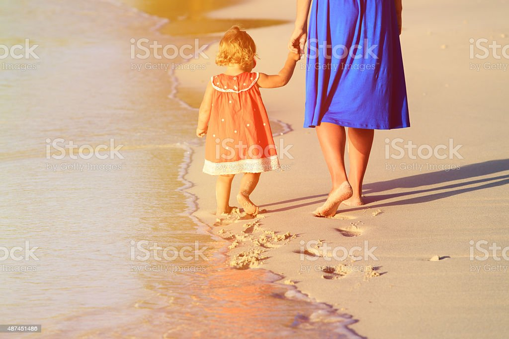 mother and little daughter walking on beach stock photo