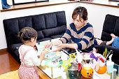 母と小さな女の子のハロウィーン パーティーのためのクッキーにアイシングを適用します。