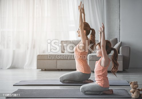 istock Mother and little girl are doing sport exercises at home 1138370611