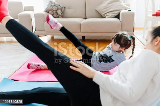 916126642 istock photo Mother and little girl are doing sport exercises at home 1216840828