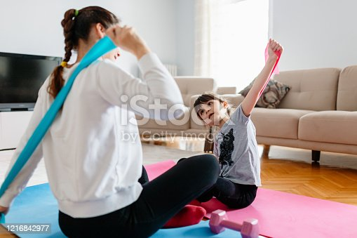 916126642 istock photo Mother and little girl are doing sport exercises at home 1216842977