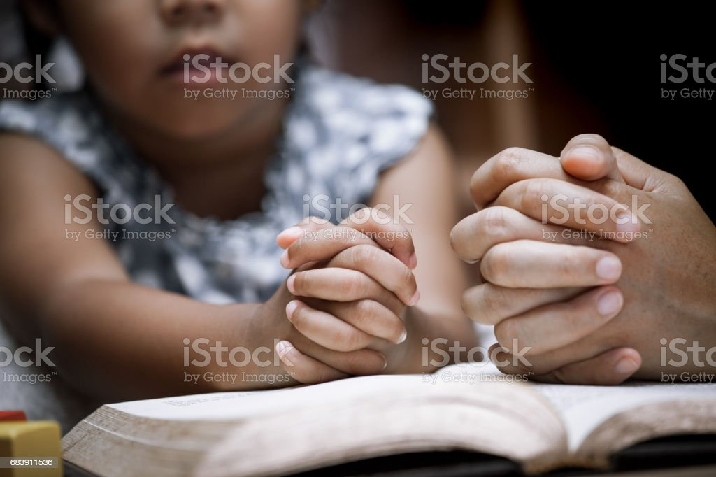 Mother and little girl hands folded in prayer on a Holy Bible together stock photo