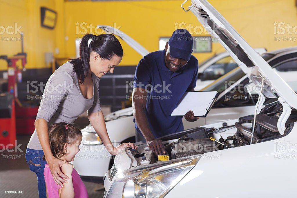mother and little girl in car service center royalty-free stock photo