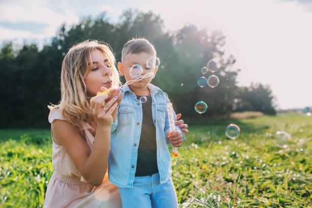 matka i synek dmuchanie bańki mydlane na zewnątrz - białoruś zdjęcia i obrazy z banku zdjęć