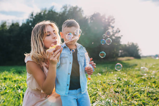 mother and little son blowing soap bubbles outdoor - białoruś zdjęcia i obrazy z banku zdjęć