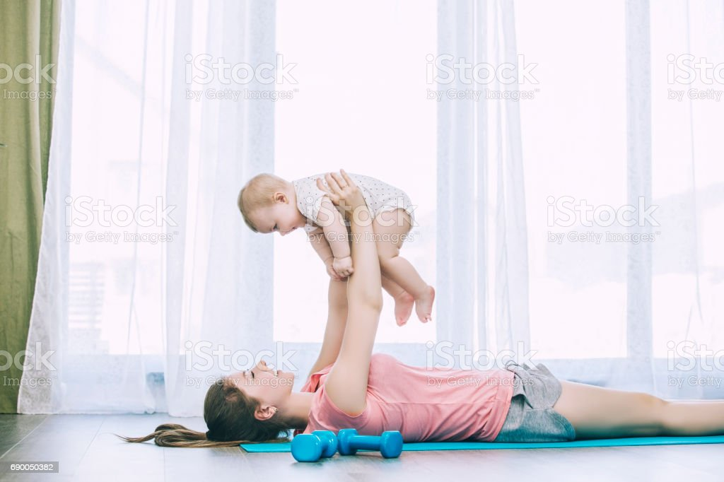 Mother and little toddler doing fitness at home on an exercise Mat together and smiling stock photo