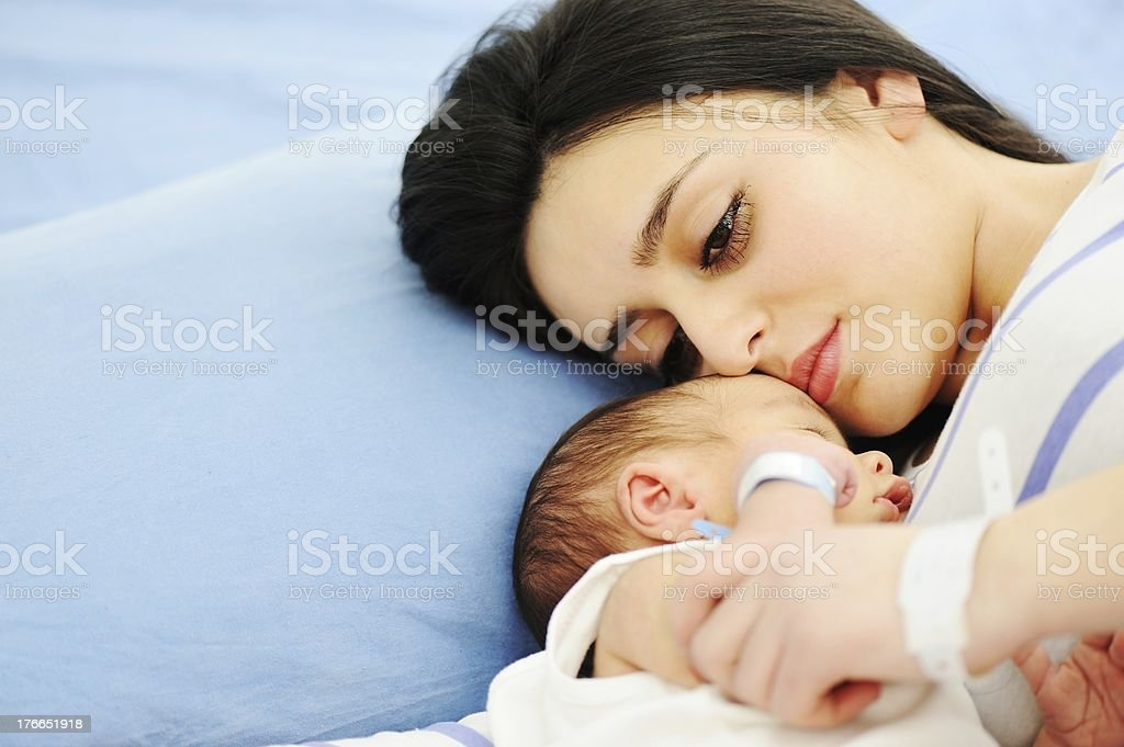 Mother and newborn lying in hospital bed stock photo