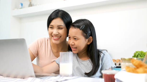 Mother and preteen daughter video call to grandparent in kitchen at home.family happy time.video conference with laptop.quarantine activity when outbreak of coronavirus.e-learning concept stock photo