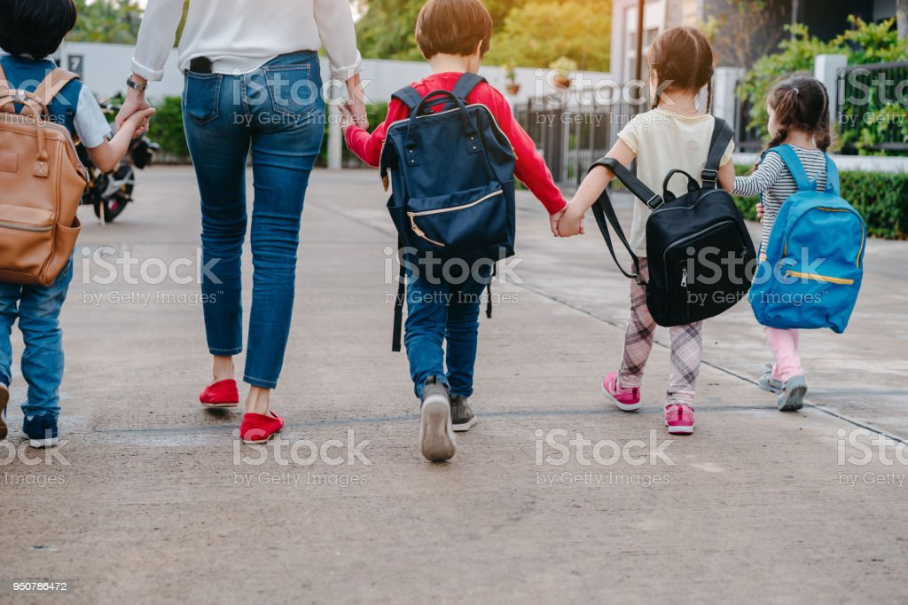 Mother and pupil and kids holding hands going to school in first class with schoolbag or satchel walking to school bus, Parent and son,sister preschool stock photo