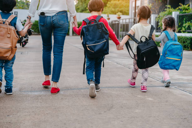 mother and pupil and kids holding hands going to school in first class with schoolbag or satchel walking to school bus, parent and son,sister preschool - gmail imagens e fotografias de stock