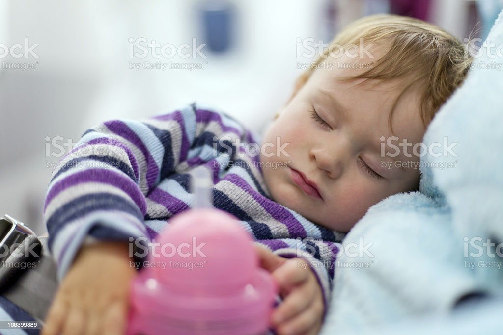 Mother and sleeping baby girl travel on airplane stock photo