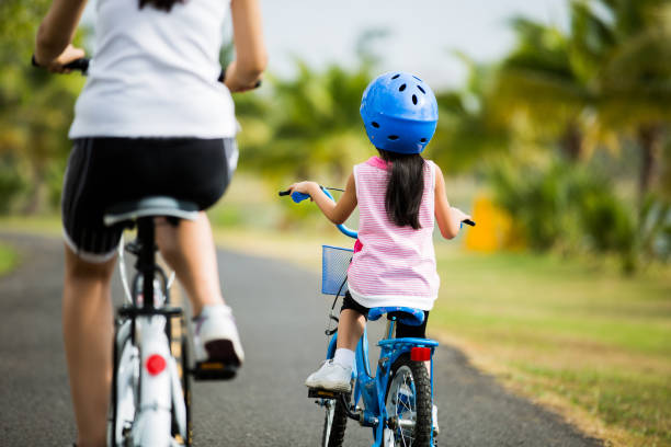 Mother and son are cycling in the park. stock photo