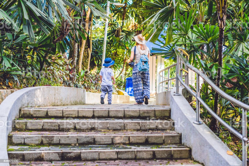Mother and son are tourists on a tropical park in Malaysia.  Central Park of Kuala Lumpur city, garden of hibiscuses. Malaysia stock photo