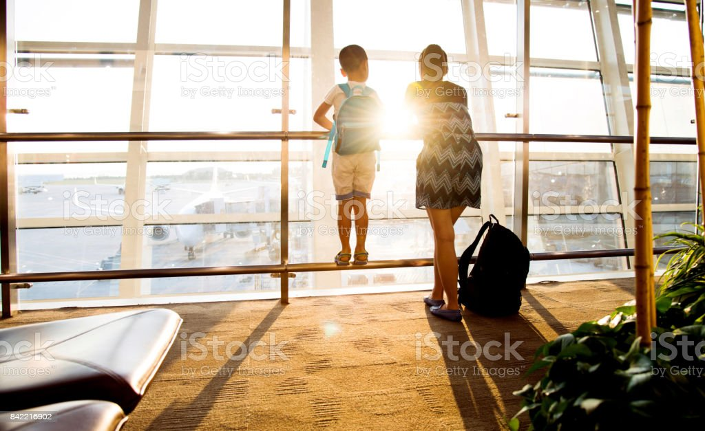 Mother and son at airport waiting for departure stock photo