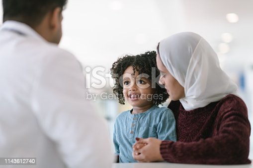 A young Muslim mother wearing a hijab takes her toddler son to visit the pediatrician. The boy is sitting on his mother's lap. They are seated at a table and a male doctor is seated across from them. The child is smiling at the doctor. The mother is looking at her son.