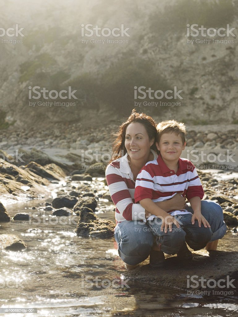 Mother and son (6-7) at seashore, backlit 免版稅 stock photo