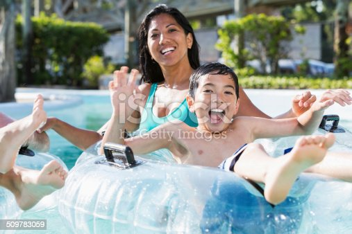 Mature woman (40s) with son (9 years, mixed race Caucasian / Pacific Islander) having fun at water park.
