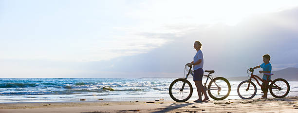 Mother and son biking at beach stock photo