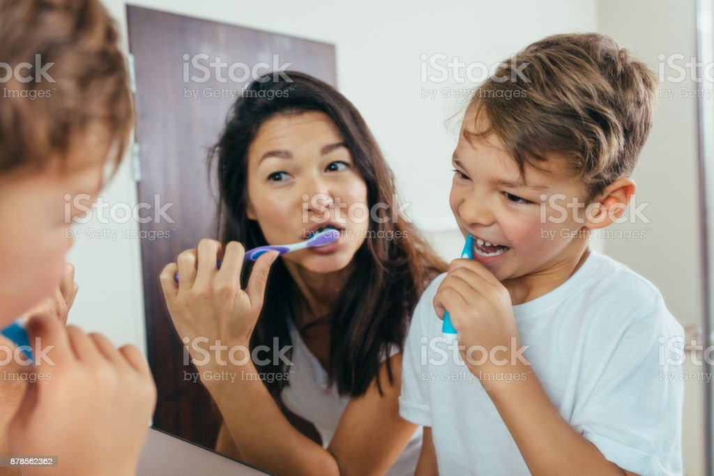 Mother and son brushing teeth in bathroom stock photo