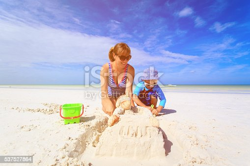 512726470 istock photo mother and son building sand castle on beach 537527864