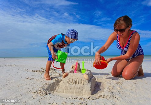 512726470 istock photo mother and son building sand castle on summer beach 468049210