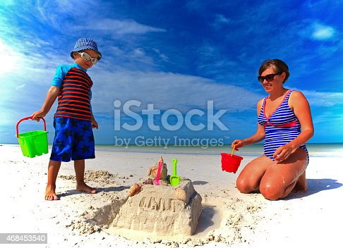 512726470 istock photo mother and son building sand castle on summer beach 468453540
