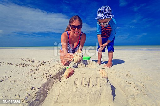 512726470 istock photo mother and son building sand castle on tropical beach 534079889
