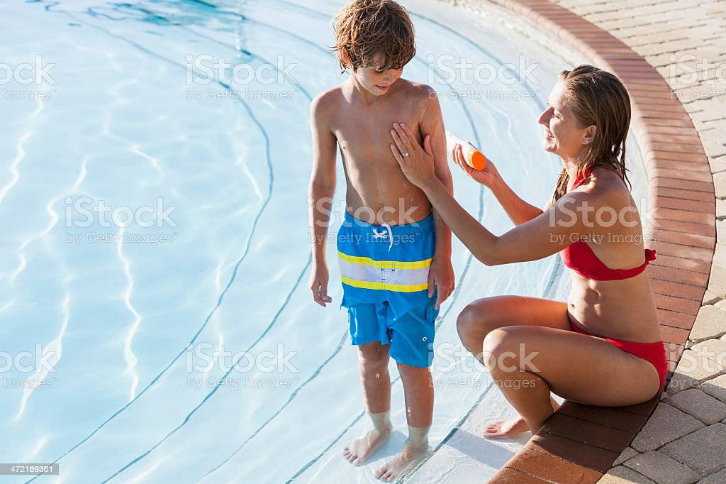 Mother and son by pool using sunscreen stock photo