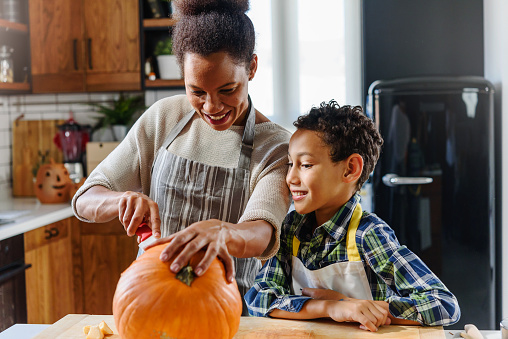 Mother and son carving pumpkin for Halloween holiday. African american ethnicity family.