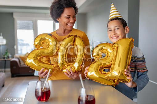 Mother and her son are at home holding 2021 balloons