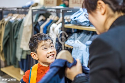 Mother and son choosing clothing indoors