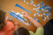 Caucasian mother and son are collecting puzzles at home. They are collaborating and are happy.