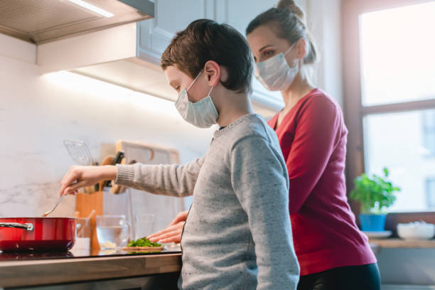 Mother and son cooking at home during the crisis time stock photo