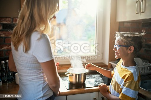 Mother and son are warming family lunch. The boy is stirring soup in the pot. Nikon D850
