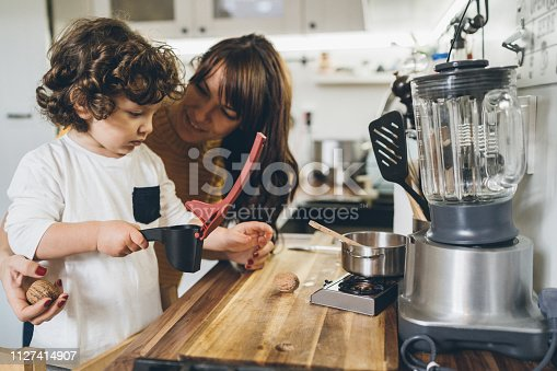 Mother and son Cracking a walnut at home in the kitchen