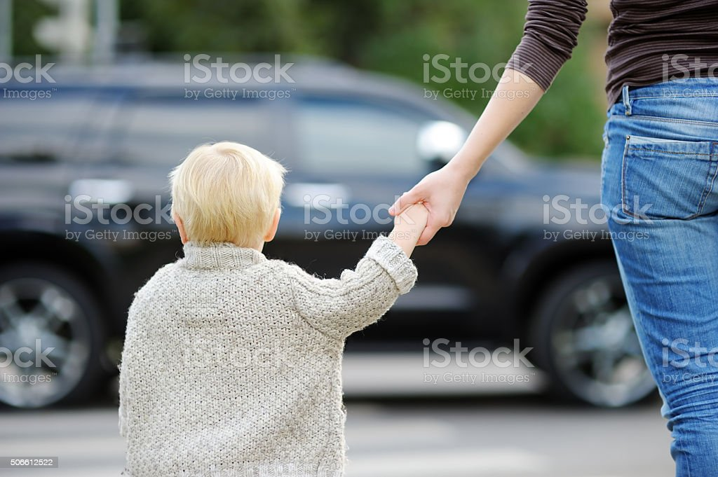 Mother and son crossing street on the crosswalk stock photo