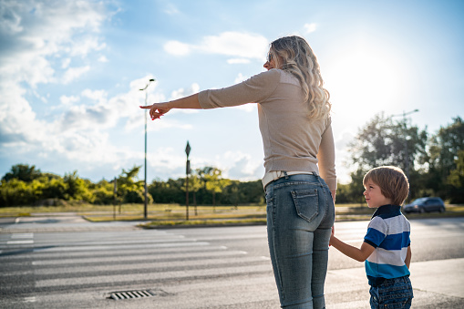 Mother is learning her son how to cross the road