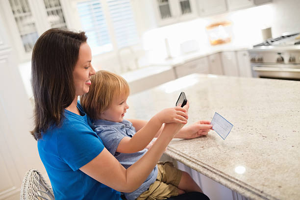 mother and son depositing check through smart phone - bank deposit slip stock pictures, royalty-free photos & images