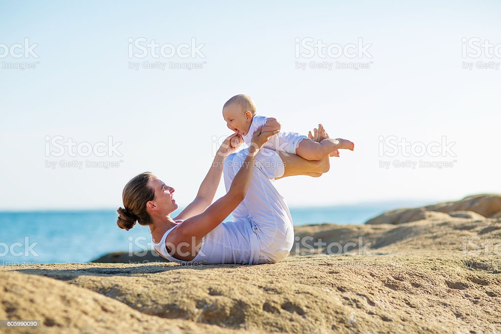 mother and son doing exercises on beach. stock photo