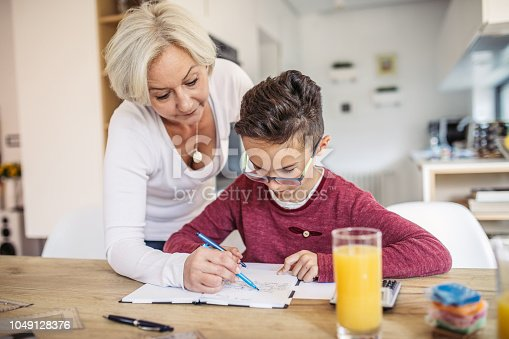 680535874 istock photo Mother and son doing homework at home 1049128376