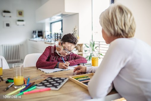 680535874 istock photo Mother and son doing homework 1049126314