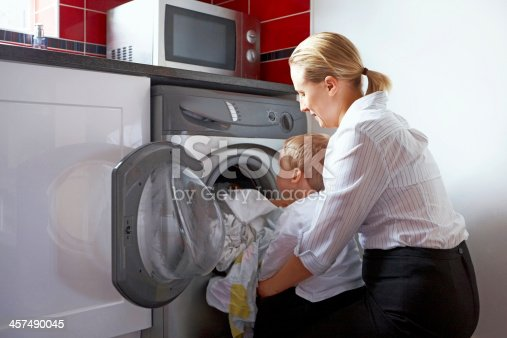 istock Mother and son doing laundry 457490045