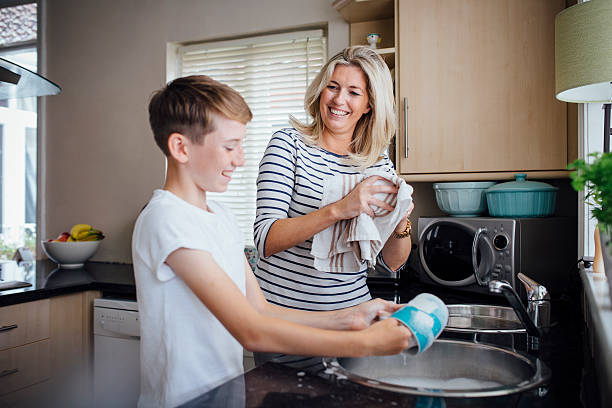 mother and son doing the dishes - singelmamma bildbanksfoton och bilder