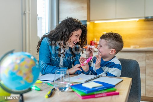 1020504438istockphoto Mother and son drawing together, mom helping with homework 1145327821