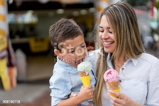 Mother and son eating an ice cream and looking very happy - family concepts