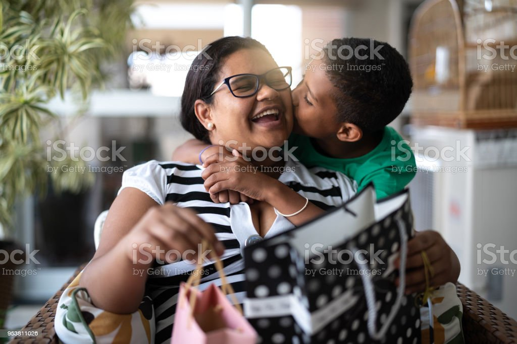 Mother and son embracing and receiving gifts - Mothers Or Children's Day stock photo